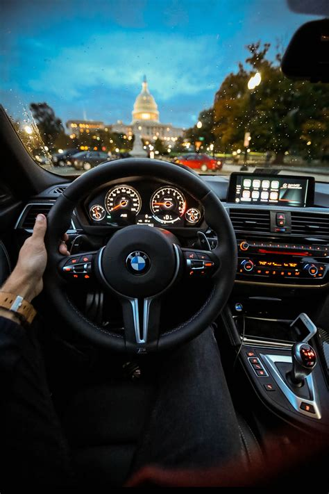 Person Holding Bmw Steering Wheel · Free Stock Photo